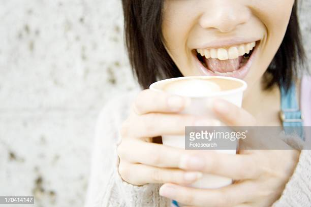 Lips of a woman drinking cafee latte