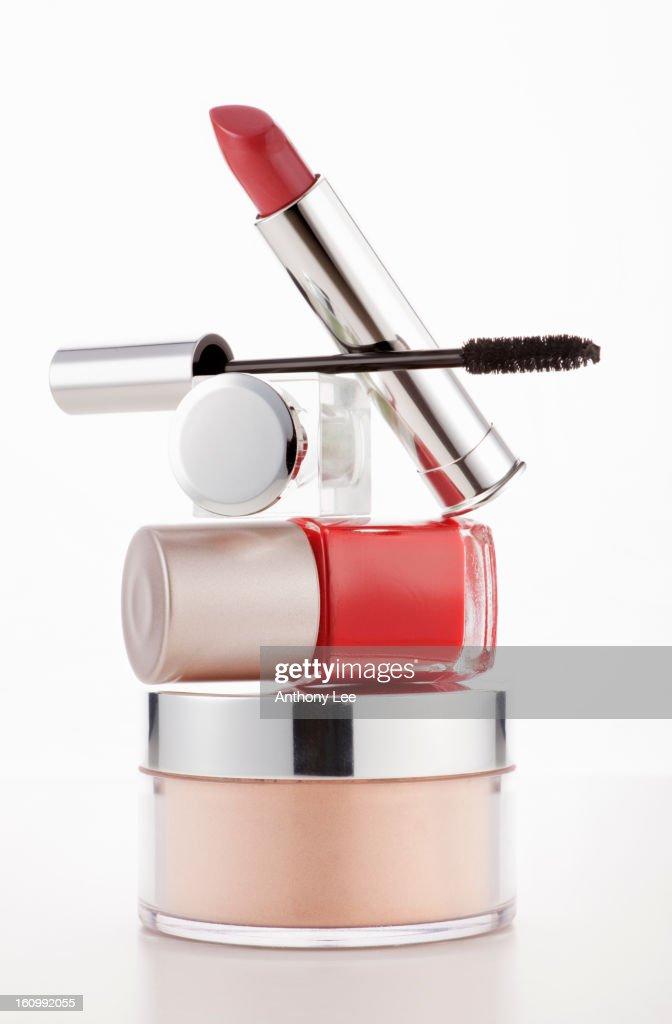'Lipstick, mascara and fingernail polish stacked on moisturizer jar' : Stock Photo