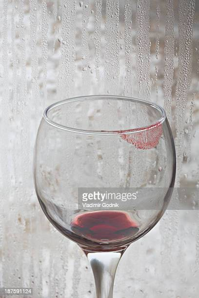 lipstick on a glass of red wine with rain covered window in the background - empty wine glass stock photos and pictures
