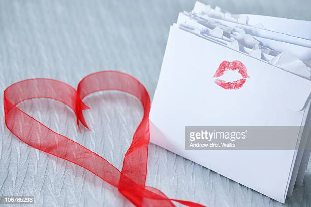 lipstick on love letters and heart-shaped ribbon - love letter stock photos and pictures