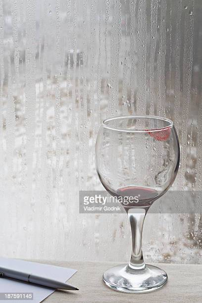 Lipstick stained wine glass beside pen and paper