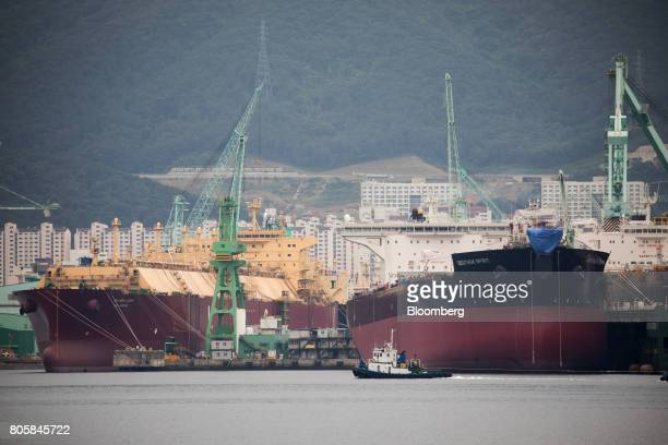 A liquefied natural gas tanker left and other ships sit under construction at the Samsung Heavy Industries Co shipyard in Geoje South Korea on...