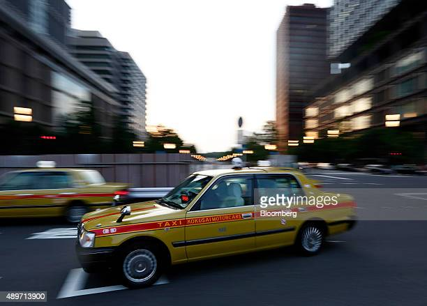 Liquefied petroleum gas powered taxies drive along a road outside a train station in Tokyo Japan on Wednesday Sept 23 2015 Tokyo's taxi companies...