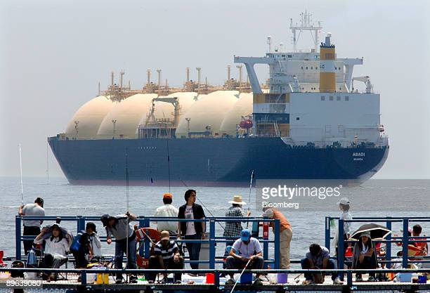 A liquefiednaturalgas tanker leaves a berth as holidaymakers fish on a pier in Yokohama City Kanagawa Prefecture Japan on Saturday June 20 2009 The...