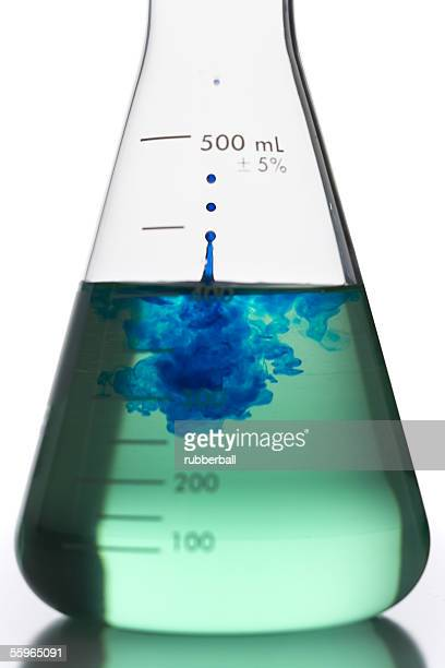Liquid being poured into a conical flask with a test tube