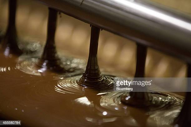 Liquid chocolate pours from nozzles onto Rodnye Prostory candies during the coating process at the Rossiya chocolate factory operated by Nestle SA in...
