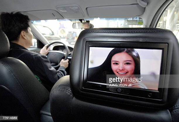 A liquid crystal display screen situated in the back of the headrest on the front passenger seat in a taxi shows advertisements in Seoul 03 January...