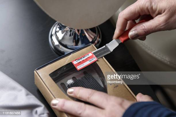 A liquidation reseller removes a clearance sticker from a BBQ utensil set to be sold online at her home in Napa California US on Thursday March 14...