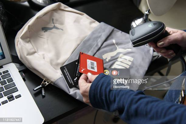 A liquidation reseller scans the tags of a Puma SE backpack to be sold online at her home in Napa California US on Thursday March 14 2019 As...
