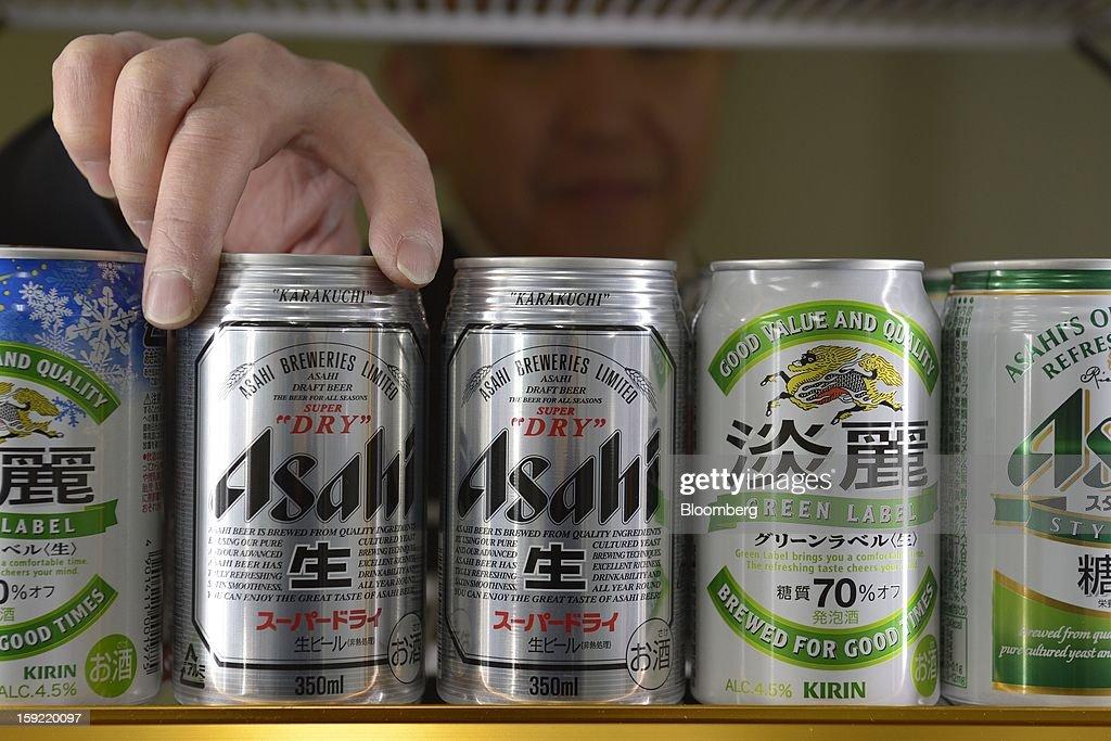 A liquor shop owner stocks cans of Asahi Breweries Ltd. Asahi Super Dry beer in Kawasaki, Kanagawa Prefecture, Japan, on Wednesday, Jan. 9, 2013. Suntory, Kirin Holdings Co. and Asahi Group Holdings Ltd., have sought growth overseas as a declining population damps domestic demand. Photographer: Akio Kon/ Bloomberg