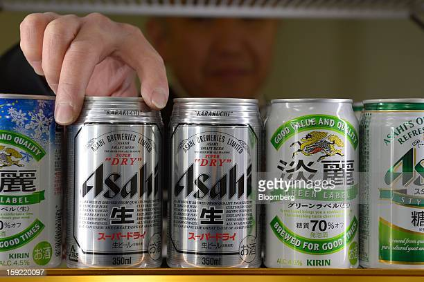 A liquor shop owner stocks cans of Asahi Breweries Ltd Asahi Super Dry beer in Kawasaki Kanagawa Prefecture Japan on Wednesday Jan 9 2013 Suntory...