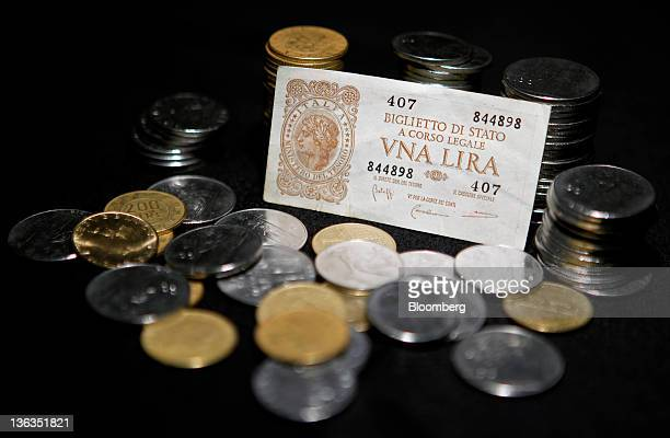 A Lira bank note from 1944 sits with mixed denominations of Lire coins Italy's former currency in this arranged photograph in Rome Italy on Sunday...