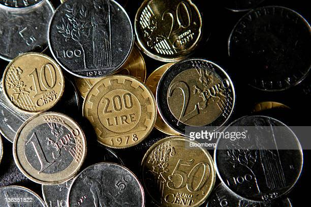 Lire coins Italy's former currency sit among mixed denominations of euro coins in this arranged photograph in Rome Italy on Sunday Jan 1 2012 Prime...