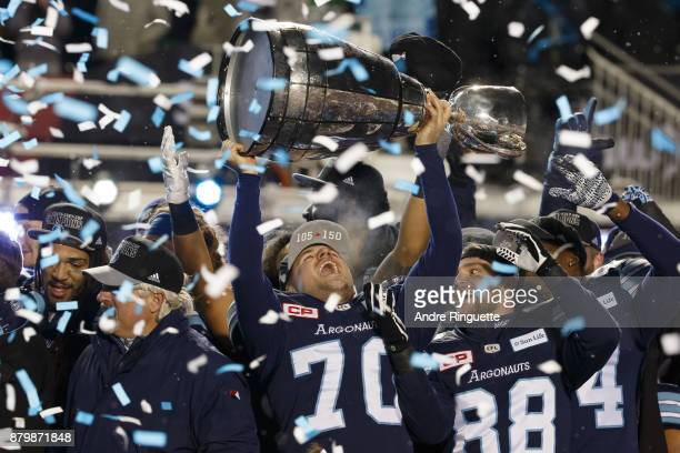 Lirim Hajrullahu of the Toronto Argonauts raises the Grey Cup after winning the 105th Grey Cup Championship Game against the Calgary Stampeders at TD...