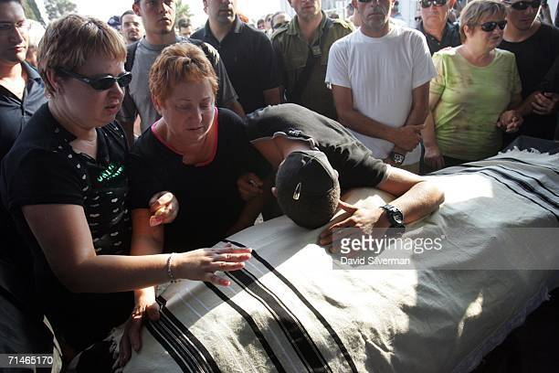 Liron Feldman cries on the prayershawl covered body of his brother David Feldman as he mourns with his mother Luba and sister Neta during his funeral...
