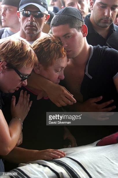 Liron Feldman the brother of slain Israeli David Feldman embraces his mother Luba and sister Neta as they mourn over the prayershawl covered body...