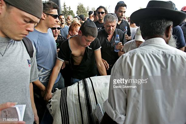 Liron Feldman the brother of slain Israeli David Feldman helps carry his brother's prayershawl covered body during his funeral July 17 2006 in the...