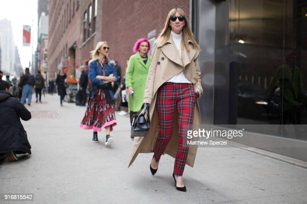 Lisa Aiken is seen on the street attending SelfPortrait during New York Fashion Week wearing red plaid pants with a khaki coat and white sweater on...