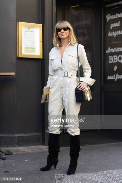 Lisa Aiken is seen on the street during Paris Fashion Week SS19 wearing white jumpsuit with black boots on September 26 2018 in Paris France
