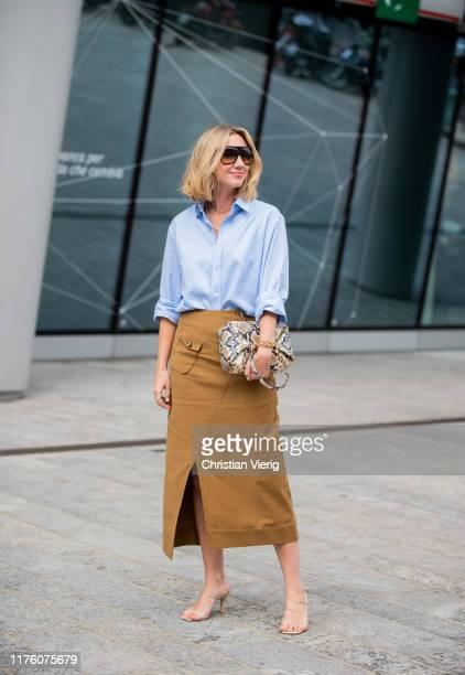 Lisa Aiken seen wearing skirt with slit, bag with snake print, blue button shirt outside the Sportmax show during Milan Fashion Week Spring/Summer...