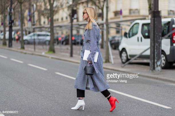 Lisa Aiken wearing a checked coat red and white boots outside Ellery on March 7 2017 in Paris France