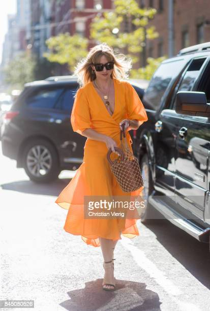 Lisa Aiken wearing an orange dress bucket bag seen in the streets of Manhattan outside SelfPortrait during New York Fashion Week on September 9 2017...