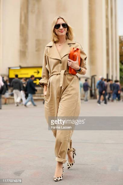 Lisa Aiken wearing beige jumpsuit, Ray-Ban sunglasses, orange clutch and leopard heels outside Rochas on September 25, 2019 in Paris, France.