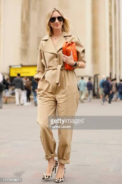 Lisa Aiken wearing beige jumpsuit, Ray-Ban sunglasses, orange clutch and leopard heels outside Rochas on September 25, 2019 in Paris, France.