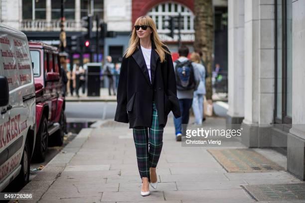 Lisa Aiken wearing checked pants black wool coat outside AWAKE during London Fashion Week September 2017 on September 19 2017 in London England