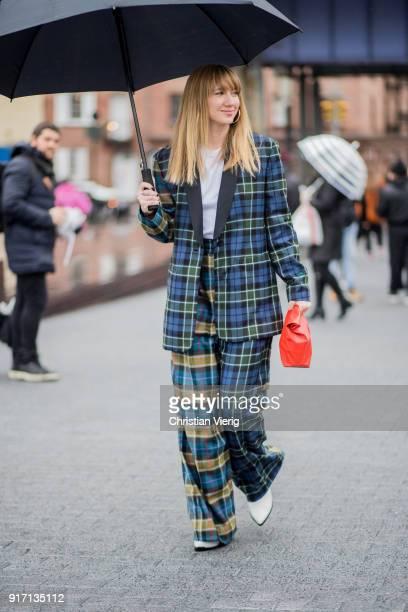 Lisa Aiken wearing checked pants checked blazer orange clutch seen outside Tibi on February 11 2018 in New York City