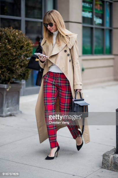 Lisa Aiken wearing lumberjack plaid pants trench coat seen outside SelfPortrait on February 10 2018 in New York City