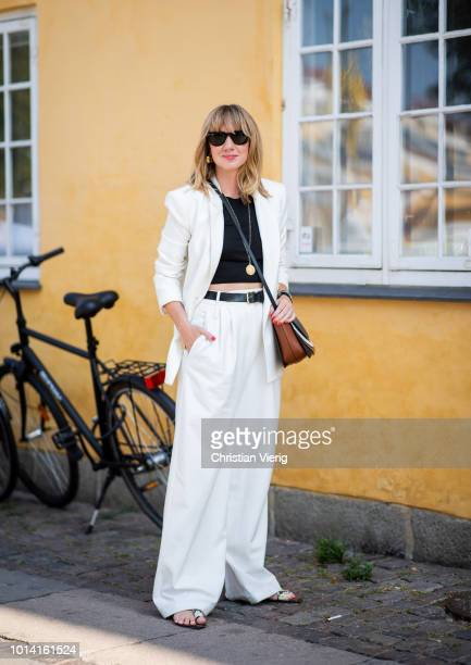 Lisa Aiken wearing white pants white blazer jacket black cropped top is seen outside Lovechild 1979 during the Copenhagen Fashion Week Spring/Summer...