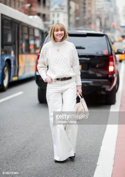 Lisa Aiken wearing white wide leg pants white knit seen outside Tory Burch on February 9 2018 in New York City