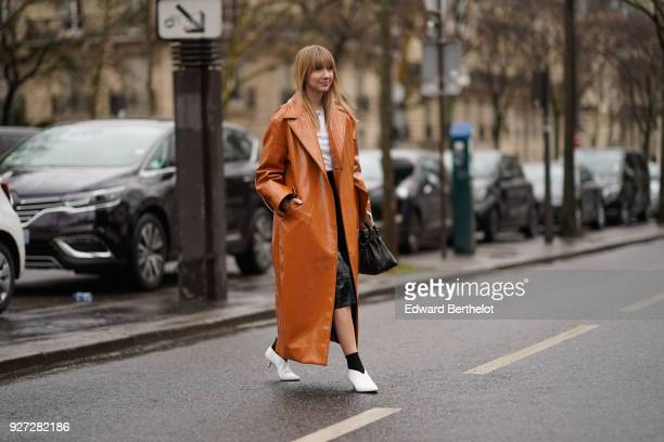 Lisa Aiken wears a brown leather trench coat white shoes during Paris Fashion Week Womenswear Fall/Winter 2018/2019 on March 4 2018 in Paris France