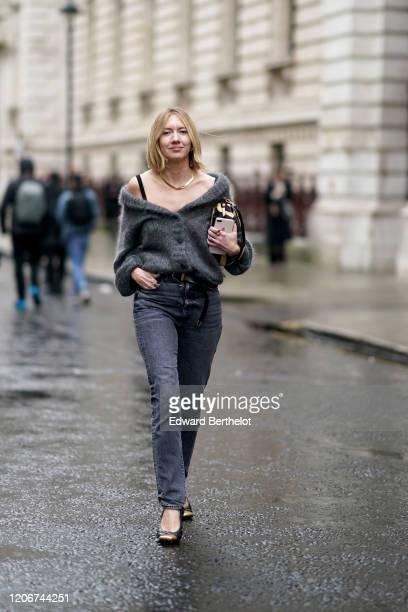 Lisa Aiken wears a golden necklace, a wool gray jacket, a belt, gray denim jeans, black shoes, a bag, during London Fashion Week Fall Winter 2020 on...