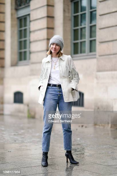 Lisa Aiken wears a gray beanie hat a white fringed jacket a white bag blue jeans black shoes outside Alexis Mabille during Paris Fashion Week Haute...