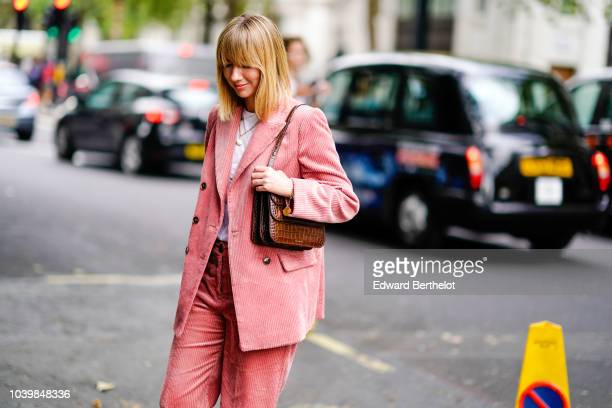 Lisa Aiken wears a pink blazer jacket pink flared pants a white tshirt a bag during London Fashion Week September 2018 on September 18 2018 in London...