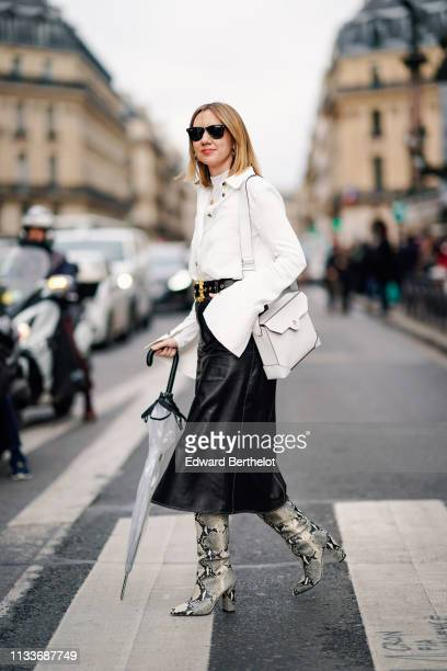 Lisa Aiken wears a white jacket with flared sleeves a white bag a black leather skirt snake print boots sunglasses holds an umbrella outside Stella...