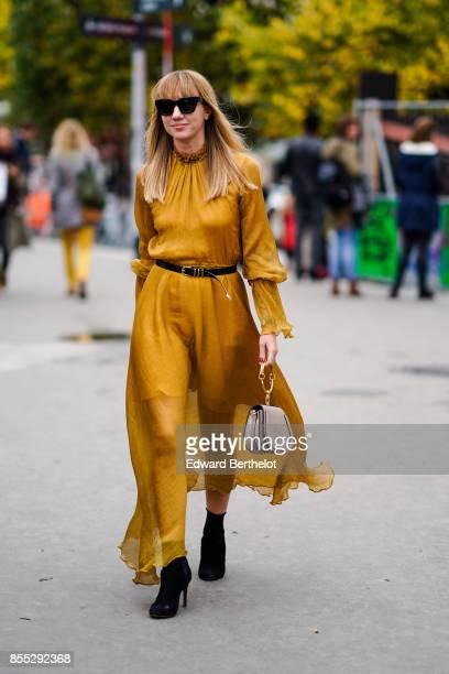 Lisa Aiken wears a yellow dress outside Ann Demeulemeester during Paris Fashion Week Womenswear Spring/Summer 2018 on September 28 2017 in Paris...