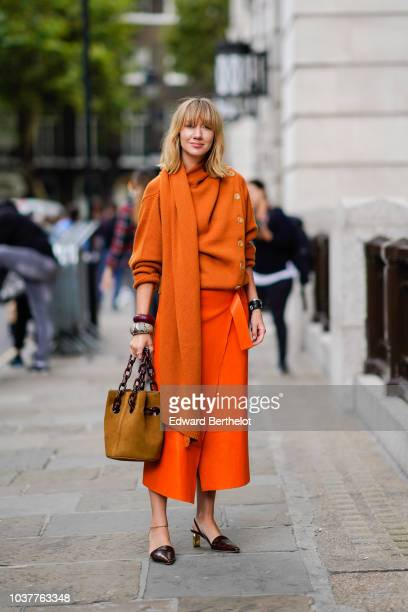 Lisa Aiken wears an orange pull over with a scarf an orange skirt a brown bag during London Fashion Week September 2018 on September 15 2018 in...