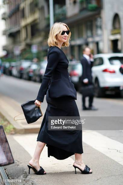 Lisa Aiken wears sunglasses, a black jacket, a black skirt, a black bag, black woven leather mules, anklets, outside the Dolce & Gabbana show during...
