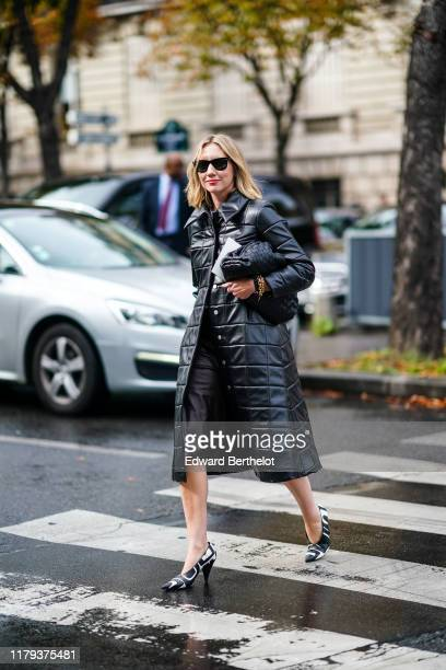 Lisa Aiken wears sunglasses a black quilted puffer long coat a bag black and white pointy shoes outside Miu Miu during Paris Fashion Week Womenswear...