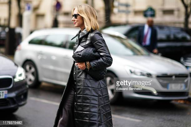 Lisa Aiken wears sunglasses a black quilted puffer long coat a bag outside Miu Miu during Paris Fashion Week Womenswear Spring Summer 2020 on October...