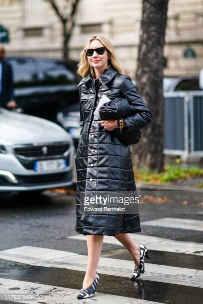 Lisa Aiken wears sunglasses, a black quilted puffer long coat, a bag, black and white pointy shoes, outside Miu Miu, during Paris Fashion Week -...