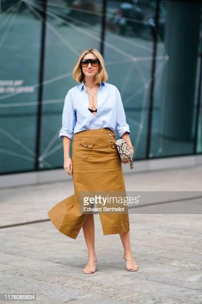 Lisa Aiken wears sunglasses, a blue open shirt, black bras, a snake print bag, brown skirt, a necklace, heels shoes, outside the Sportmax show during...