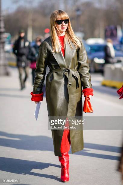 Lisa Aiken wears sunglasses, a green leather trench coat, a red dress, a red bag, red boots , during Paris Fashion Week Womenswear Fall/Winter...