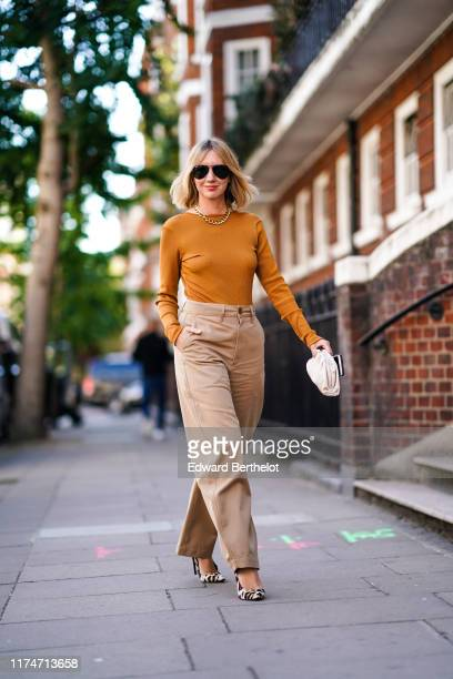 Lisa Aiken wears sunglasses a necklace an orange top flare pants leopard print shoes during London Fashion Week September 2019 on September 14 2019...