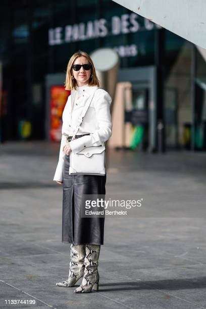 Lisa Aiken wears sunglasses a white shirt a white bag a black leather skirt beige python pattern boots outside Giambattista Valli during Paris...