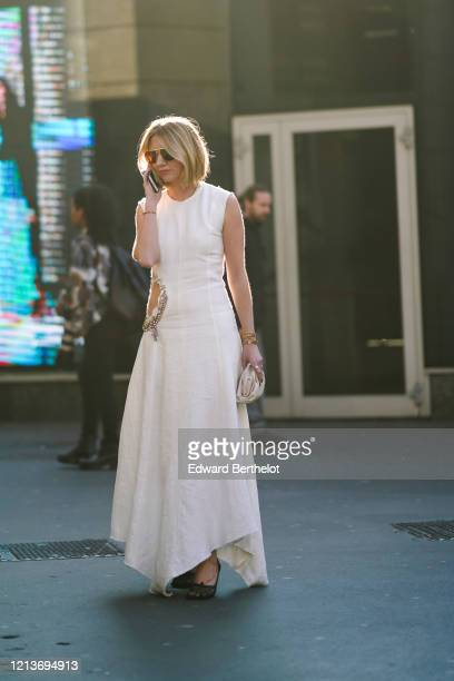 Lisa Aiken wears sunglasses, bracelets, rings, a ripped hem white dress with a bejeweled slot at the waist and a handkerchief hem, a beige quilted...