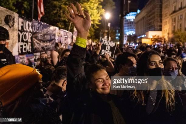 Lisa Alcindor of Alexandria, VA, Angelique McKenna of Arlington, VA and Vivan Mora of Arlington, VA cheer while listening to President-elect Joe...